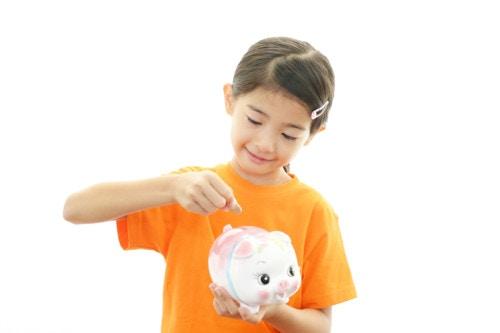 貯金箱にお金を入れる子供
