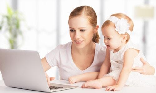 赤ちゃんとPCを見るママ